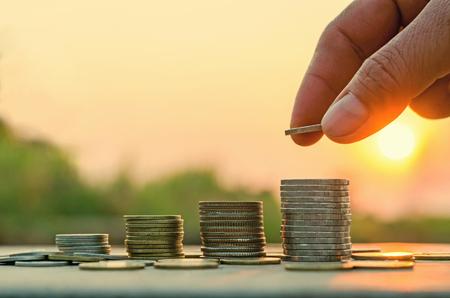 Main mettant de l'argent sur la pile de pièces de monnaie avec idée de concept Economie d'argent et fond de coucher du soleil de la nature Banque d'images - 73940272