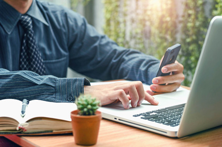 Image of business person using laptop at desk and mobile phone
