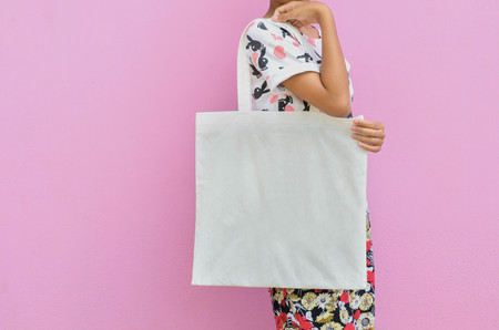 Mock-up Girl is holding blank cotton bag. Handmade eco shopping bag for girls and pink background