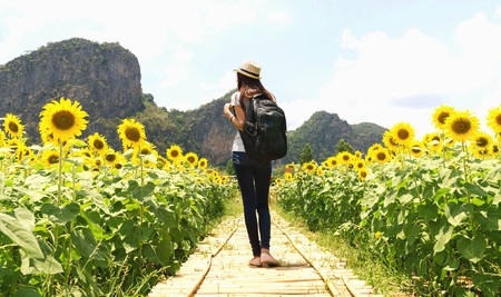 profesional: Traveling woman with backpack and straw hat looking sunflower in field Stock Photo