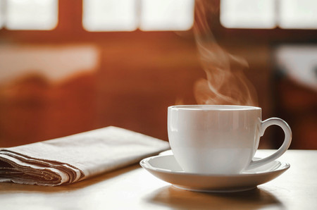 coffee cup with newspaper on the table, coffee shop background, warm tone Stock Photo