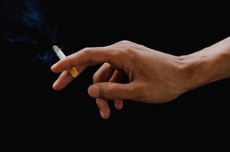 hand holding cigarette and smoke on black Stok Fotoğraf