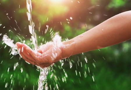 Water gieten splash in de hand en natuur achtergrond met zonneschijn