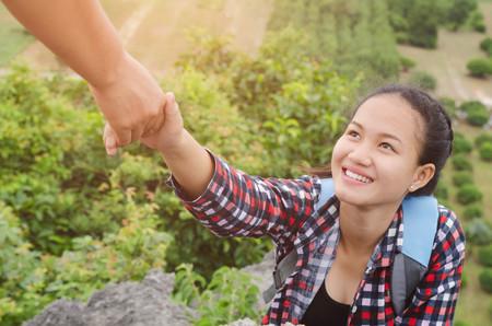 Hand houden helpen jonge vrouw reiziger op de top berg Stockfoto