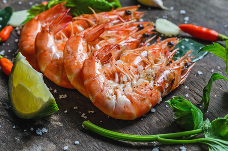 grill: close up shrimps and lemon with chilli on wood background Stock Photo