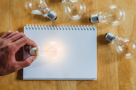 concept hand and light bulb isolate on notebook background Stock Photo