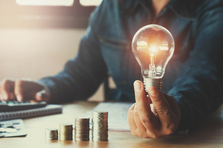 business accountin with saving money with hand holding lightbulb concept financial background Stockfoto