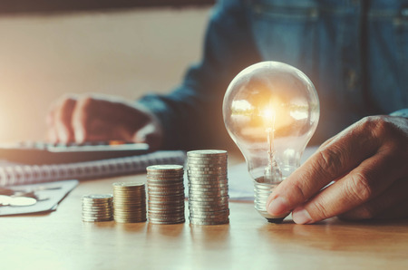 business accountin with saving money with hand holding lightbulb concept financial background Stok Fotoğraf