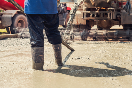 Pouring concrete with worker mix cement at construction site Stock Photo