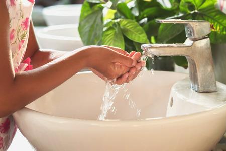 Children washing hand under faucet in basin Stock Photo