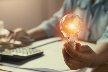 hand woman accountant holding light bulb, new idea with innovation concept