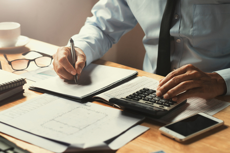 businessman working on desk office with using a calculator to calculate the numbers, finance concept Stock Photo