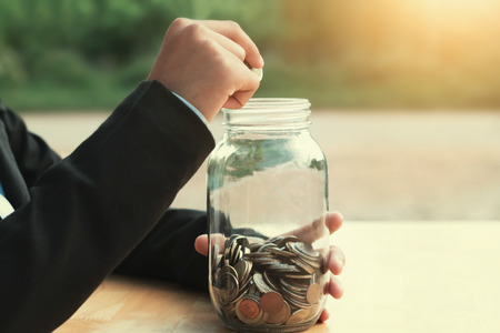 business hand putting coins in glass jar, idea saving money finance concept with sunshine