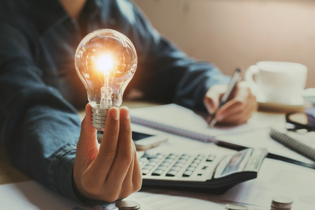 New idea and creative concept for business woman hand holding light bulb in office Reklamní fotografie