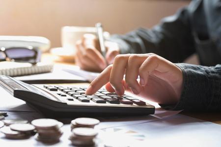 zakenvrouw met behulp van rekenmachine voor het berekenen van financiële boekhouding in kantoor
