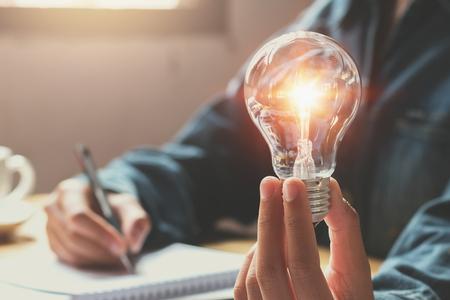 nowy pomysł i koncepcja kreatywna biznes kobieta ręka trzyma żarówkę