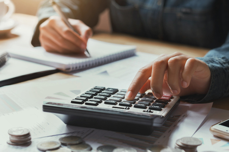 close up hand businesswoman using calculator for calculate finance accounting in office Stock Photo