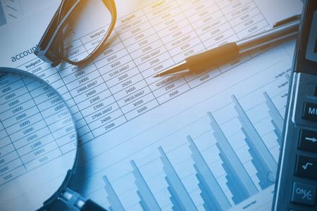 contabilità documenti aziendali con calcolatrice, penna, occhiali e lente d'ingrandimento. concetto finanziario