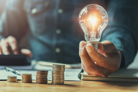 business man hand holding lightbulb with using calculator to calculate and money stack. idea saving energy and accounting finance in office concept Standard-Bild