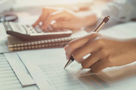 Buchhalter arbeitet am Schreibtisch mit Taschenrechner mit Stift