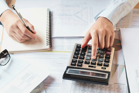 accountant working on desk to using calculator with pen on book .concept finance