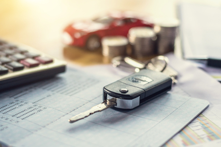 car key with money and calculator on table.