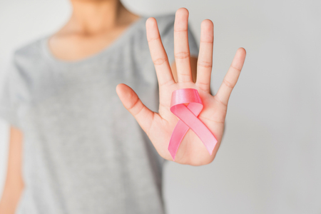 womaen hand holding pink ribbon cancer awareness. concept healthcare and medicine