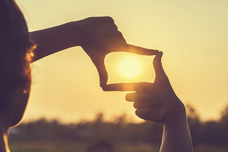 Hand framing view distant over sunset Stock Photo
