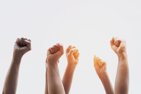 Gruppenmenschen von Fäusten, die mit Sonnenlicht erhoben werden