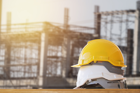 Yellow and white safety helmet on the table in construction site background