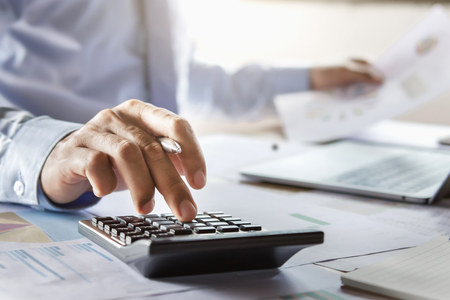 accountant working on desk using calculator for calculate finance report in office