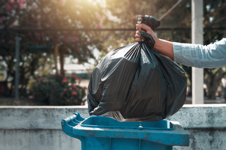 hand holding garbage black bag putting in to trash Stock Photo