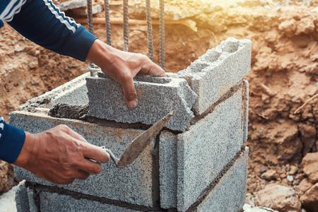 Arbeiter, der Ziegel auf der Baustelle installiert