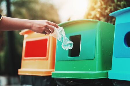 people hand holding garbage bottle plastic putting into recycle bin for cleaning Banco de Imagens
