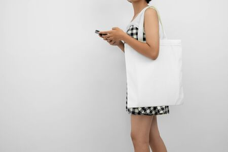 young woman holding eco cotton bag and using mobile isolate on white background Stok Fotoğraf - 130721659