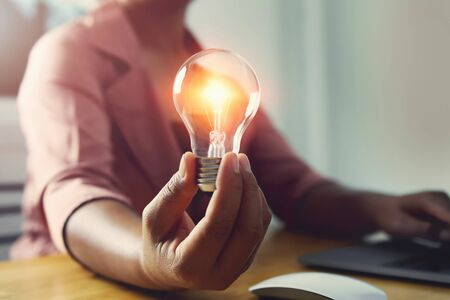hand holding light bulb with using laptop in office. concept saving energy power Stok Fotoğraf - 130721662