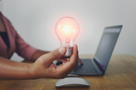 business woman hand holding light bulb with using laptop in office. concept saving energy power Stok Fotoğraf - 130721666