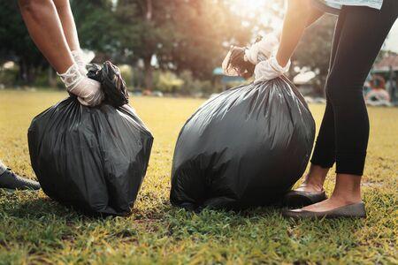 mother and children keeping garbage black bag at park in morning light Stok Fotoğraf