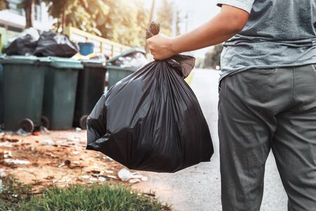 woman hand holding garbage in black bag for cleaning in to trash Stok Fotoğraf - 130721526