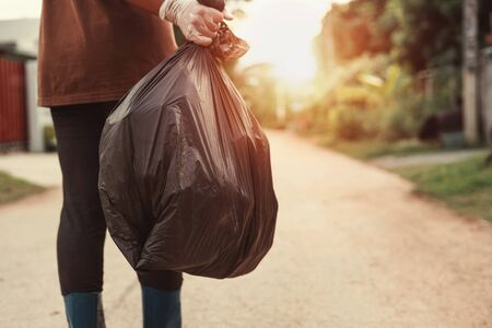 woman hand holding garbage bag for recycle putting in to trash Stok Fotoğraf - 130721537