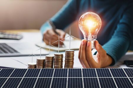 businesswoman holding light bulb with turbine on coins and solar panel. concept saving energy and finance accounting Stok Fotoğraf