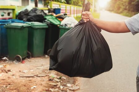 woman hand holding garbage in black bag for cleaning in to trash
