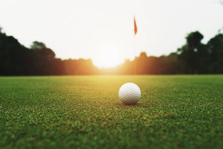 golf ball on green grass with hole and sunlight Stok Fotoğraf - 130721475