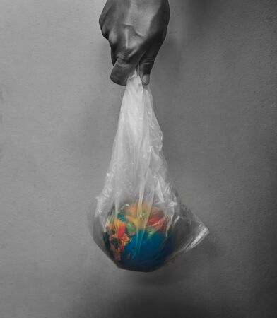 hand holding globe in plastic bag on black background concept earth day Stok Fotoğraf