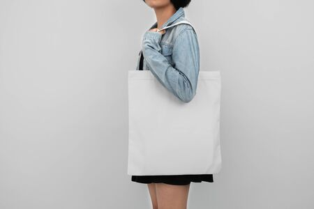 young woman holding eco cotton bag isolate on white background