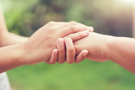 personnes âgées et jeunes main tenant avec la lumière du soleil. puissance conceptuelle de l'espoir