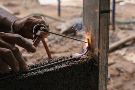 closeup hand welding metal in construction site