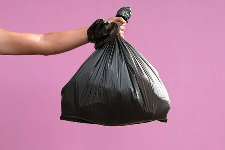 hand holding garbage bag isolate on pink background Stok Fotoğraf - 130721202