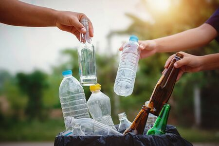 people hand holding garbage bottle plastic and glass putting into recycle bag for cleaning Stok Fotoğraf - 130721220