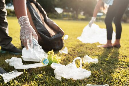 mother and children keeping garbage plastic bottle into black bag at park in morning light